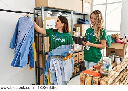 Two young volunteers woman smiling happy working at charity center.
