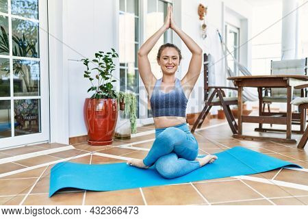 Beautiful caucasian woman training and stretching at the terrace at her home. Doing asana and wellbeing work out on yoga mat.