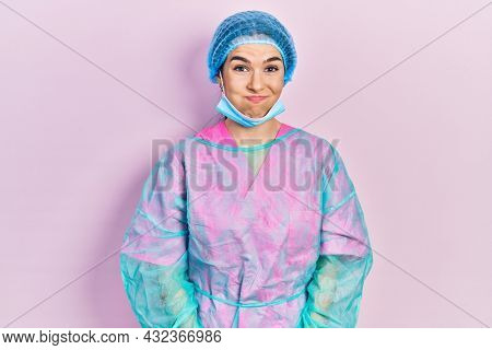 Young brunette woman wearing surgeon uniform and medical mask puffing cheeks with funny face. mouth inflated with air, crazy expression.