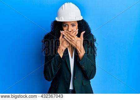 Middle age african american woman wearing architect hardhat shocked covering mouth with hands for mistake. secret concept.