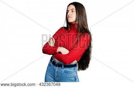 Young brunette teenager wearing red turtleneck sweater looking to the side with arms crossed convinced and confident