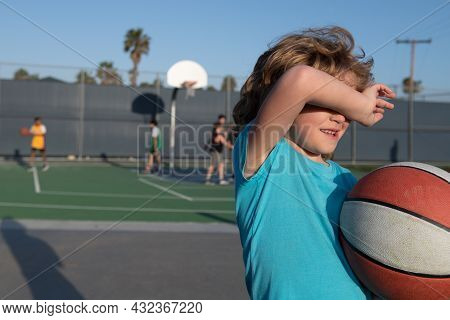 Tired Young Kid Boy From Playing Basketball. Tired Kids Sport Emotion. Child After Playing Basketbal
