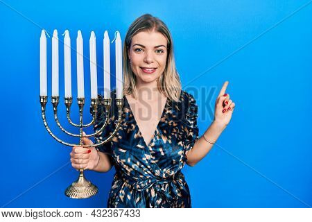 Beautiful caucasian woman holding menorah hanukkah jewish candle smiling happy pointing with hand and finger to the side