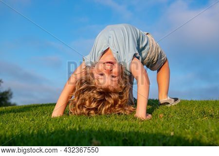 Happy Kid Girl Standing Upside Down On Her Head On Grass In Summer Day.