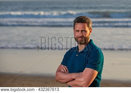 Portrait Of Man On Beach. Smiling Man With Crossed Arms By The Sea, Toothy Smile Middle Age Man.