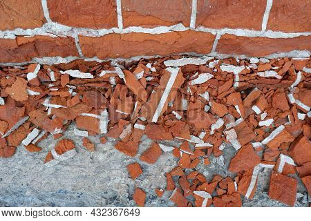 Small Fragments Of Red Brick Fell From The Old Street Wall.worn-out Facade Of The Building, Violatio