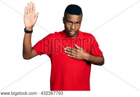 Young african american man wearing casual red t shirt swearing with hand on chest and open palm, making a loyalty promise oath