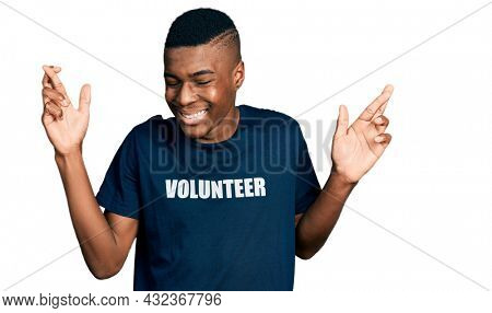 Young african american man wearing volunteer t shirt gesturing finger crossed smiling with hope and eyes closed. luck and superstitious concept.