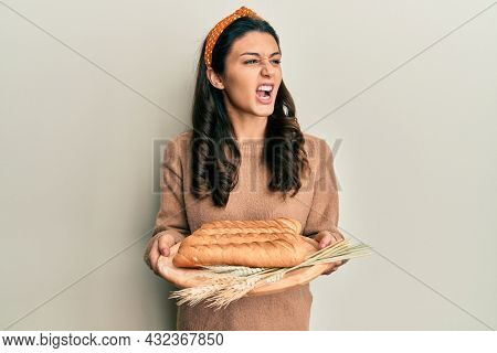 Young hispanic woman holding bread angry and mad screaming frustrated and furious, shouting with anger. rage and aggressive concept.