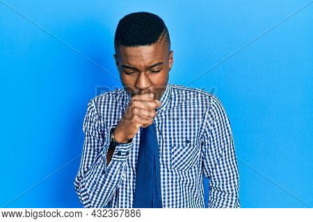 Young african american man wearing business shirt and tie feeling unwell and coughing as symptom for cold or bronchitis. health care concept.