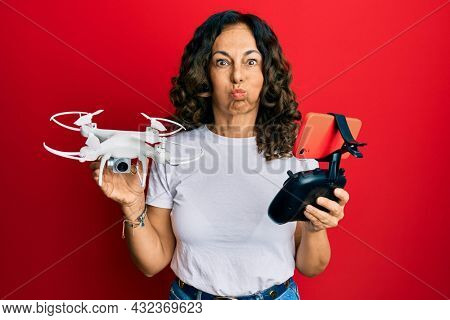 Middle age hispanic woman using drone puffing cheeks with funny face. mouth inflated with air, catching air.