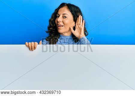 Middle age hispanic woman holding blank empty banner smiling with hand over ear listening an hearing to rumor or gossip. deafness concept.