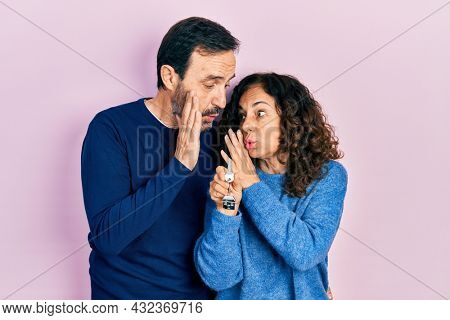 Middle age couple of hispanic woman and man holding keys of new home hand on mouth telling secret rumor, whispering malicious talk conversation