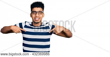 Young african american man wearing casual clothes and glasses looking confident with smile on face, pointing oneself with fingers proud and happy.