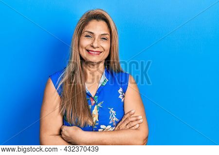 Middle age hispanic woman wearing casual clothes happy face smiling with crossed arms looking at the camera. positive person.