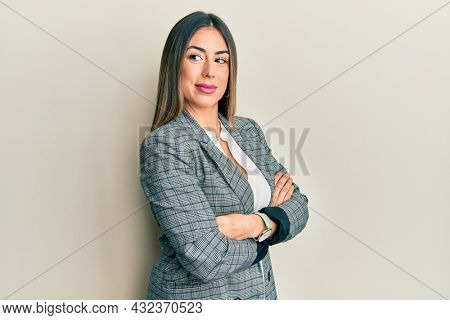 Young hispanic woman wearing business clothes with arms crossed gesture smiling looking to the side and staring away thinking.