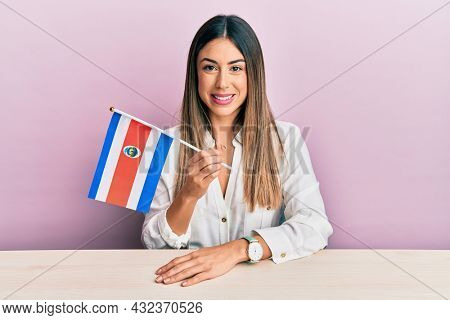 Young hispanic woman holding costa rica flag sitting on the table looking positive and happy standing and smiling with a confident smile showing teeth