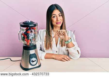 Young hispanic woman sitting on the table with food processor mixer machine with fruits with angry face, negative sign showing dislike with thumbs down, rejection concept