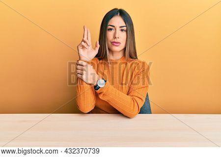 Young hispanic woman wearing casual clothes sitting on the table holding symbolic gun with hand gesture, playing killing shooting weapons, angry face