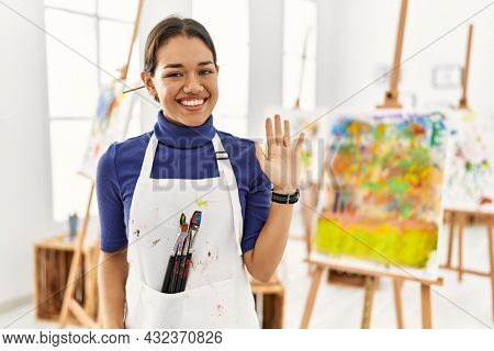 Young brunette woman at art studio waiving saying hello happy and smiling, friendly welcome gesture
