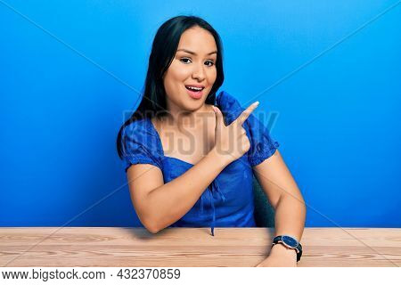 Beautiful hispanic woman with nose piercing sitting on the table cheerful with a smile of face pointing with hand and finger up to the side with happy and natural expression on face
