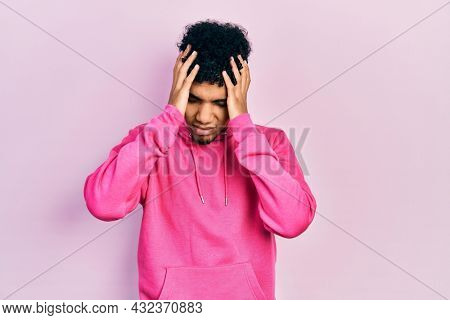 Young african american man wearing casual sweatshirt suffering from headache desperate and stressed because pain and migraine. hands on head.