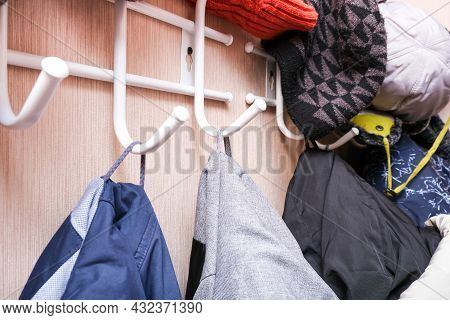 Many Winter Coats And Caps, Hats Hanging In A Mess On Hooks In A Corridor, Decluttering Warm Clothes