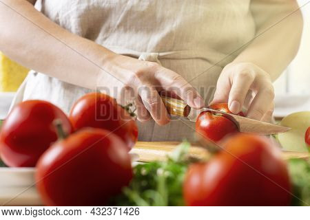 Chef Slicing Tomato Using Knife On The Table In Restaurant. Process Of Cutting And Preparation Food