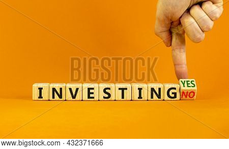 Investing Yes Or No Symbol. Businessman Turns A Wooden Cube And Change Words 'investing No' To 'inve