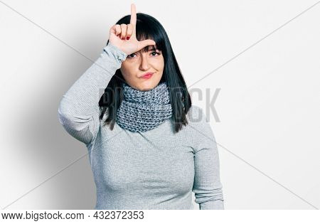 Young hispanic plus size woman wearing winter scarf making fun of people with fingers on forehead doing loser gesture mocking and insulting.