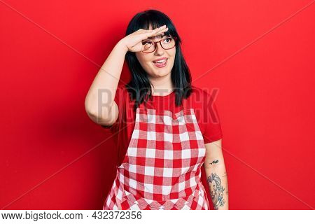 Young hispanic woman wearing cook apron and glasses very happy and smiling looking far away with hand over head. searching concept.