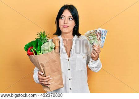 Young hispanic woman holding groceries bag and peruvian sol banknotes smiling looking to the side and staring away thinking.