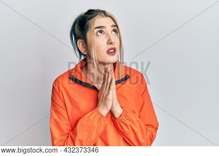 Young modern girl wearing sports sweatshirt begging and praying with hands together with hope expression on face very emotional and worried. begging.