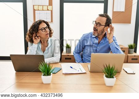 Middle age hispanic woman and man sitting with laptop at the office smiling with hand over ear listening an hearing to rumor or gossip. deafness concept.