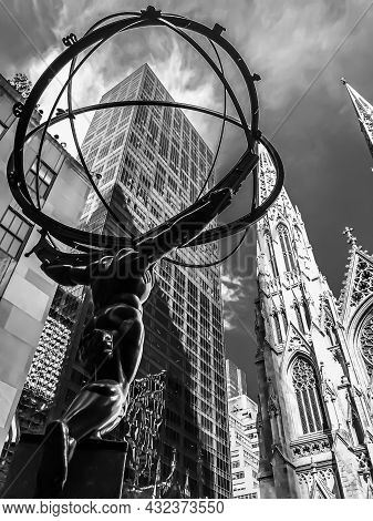 A Rear, Diagonal Shot Of The Atlas Statue Next To An Office Skyscraper And St. Patrick\'s Cathedral
