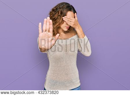 Beautiful young caucasian woman wearing casual clothes covering eyes with hands and doing stop gesture with sad and fear expression. embarrassed and negative concept.
