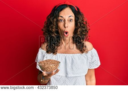Middle age hispanic woman holding bowl with lentils scared and amazed with open mouth for surprise, disbelief face