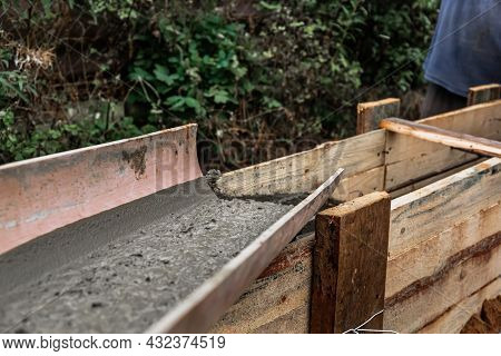 The Concrete Mixer Unloads The Concrete Through A Chute Into A Timber Formwork With Metal Reinforcem