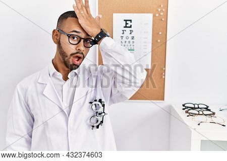 African american optician man standing by eyesight test surprised with hand on head for mistake, remember error. forgot, bad memory concept.