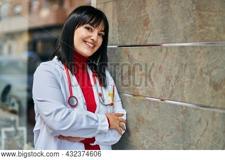 Young brunette woman wearing doctor uniform and stethoscope leaning on the wall