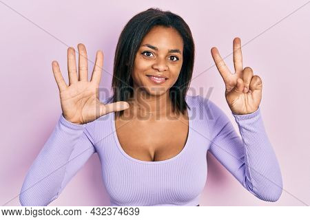 Young african american girl wearing casual clothes showing and pointing up with fingers number seven while smiling confident and happy.