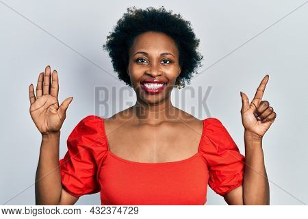 Young african american woman wearing casual clothes showing and pointing up with fingers number seven while smiling confident and happy.