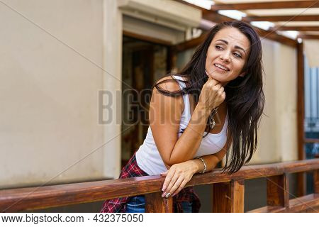 Happy Smiling Woman Standing On Veranda. Caucasian Brunette Girl In Casual Clothes. Wooden Porch Ter
