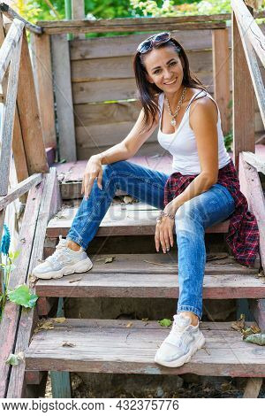 Happy Woman In Casual Clothes Is Sitting On The Steps On The Porch And Smiling. Caucasian Girl In A