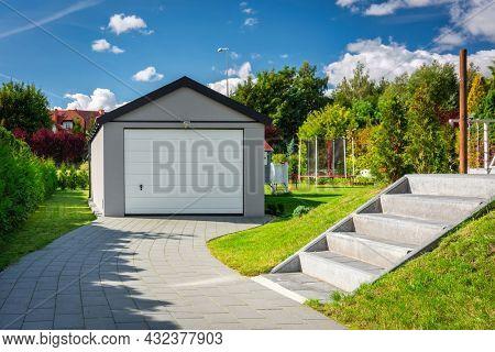 A detached garage in a green garden at summer
