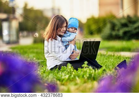 Woman On Maternity Leave Works Remotely Online Outside Sits In Front Of Laptop With Baby In Her Arms