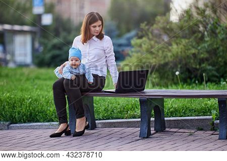 Young Mother With Baby In Her Knees Remote Work Online Using Laptop With An Internet Connection Outd