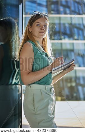 Young Woman Makes Notes In Diary While Standing Near An Office Building.
