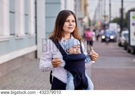 Young Woman Uses Baby Carrier Or Sling While Walking Outside With Her Four Month Old Son.