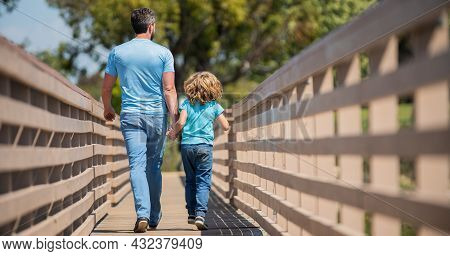 Parenting And Fatherhood. Fathers Day. Happy Father And Son Walking Outdoor Back View.